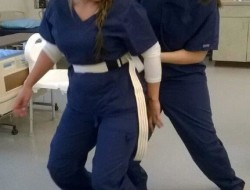 Two female students demonstrating how to use a gait belt